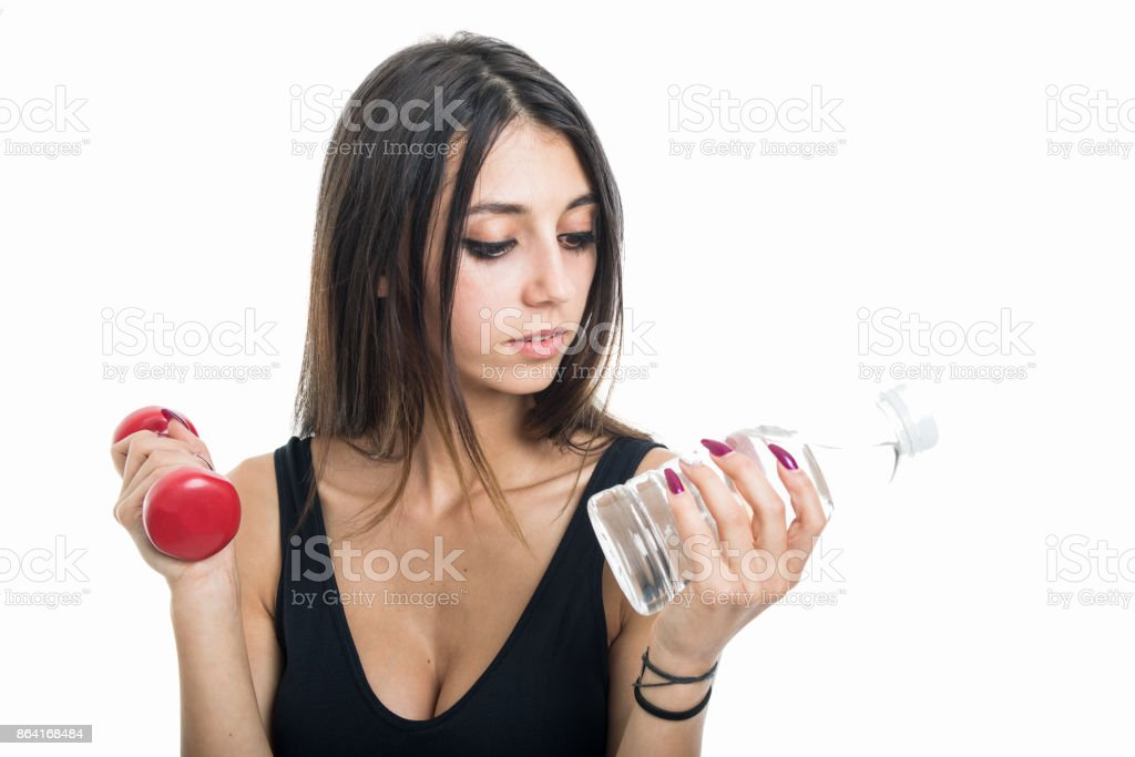 Portrait of fit girl holding water and dumbbell royalty-free stock photo
