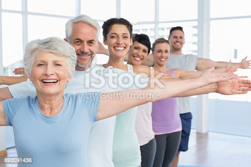 istock Portrait of fitness class stretching hands in row 693091436