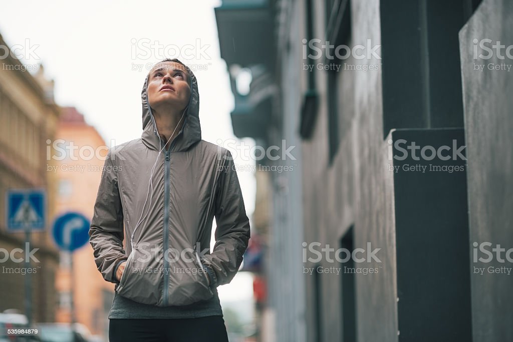 Portrait of fitness woman standing near building in rainy city stock photo