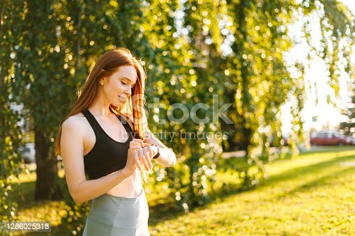 Portrait of fitness woman touch on the screen of the smart watch on her wrist to setting fitness app before running. Female at city park in sunny summer morning preparing sporty training,