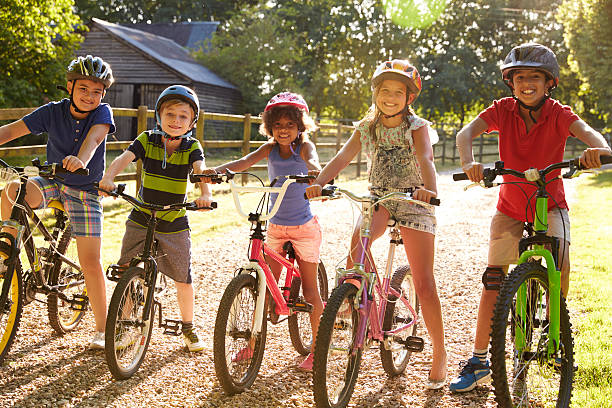 Portrait Of Five Children On Cycle Ride Together - foto stock