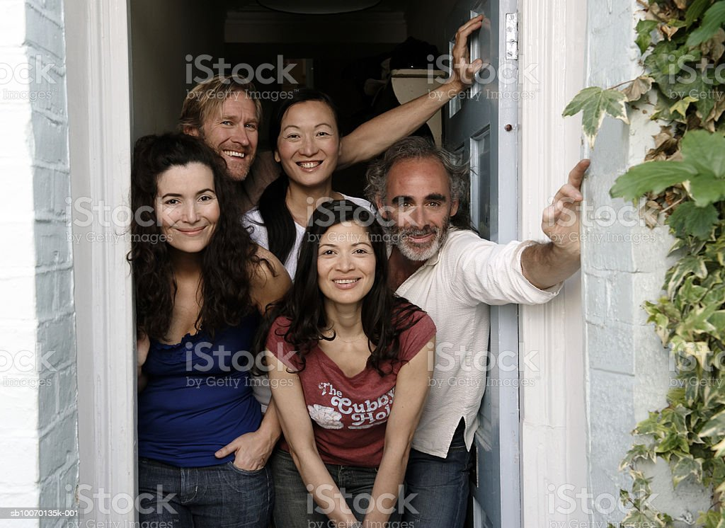 Portrait of five friends in doorway of house royalty-free stock photo
