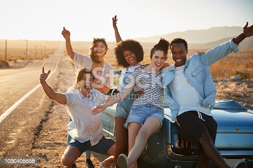1030408008 istock photo Portrait Of Five Friends Standing By Convertible Classic Car On Road Trip 1030405558