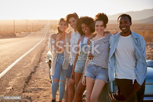 1030408008 istock photo Portrait Of Five Friends Standing By Convertible Classic Car On Road Trip 1030405562