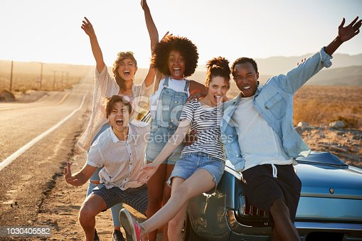 1030408008istockphoto Portrait Of Five Friends Standing By Convertible Classic Car On Road Trip 1030405582