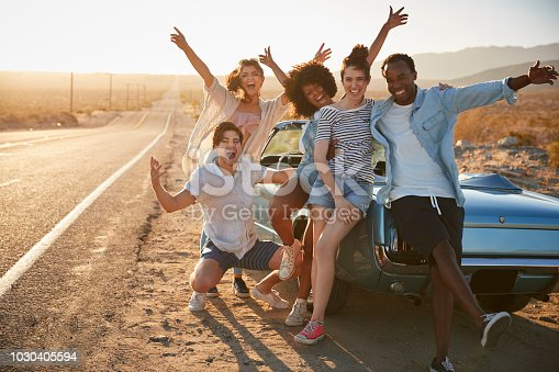 1030408008 istock photo Portrait Of Five Friends Standing By Convertible Classic Car On Road Trip 1030405594