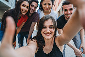 Portrait of five friends together in the city. Hispanic and caucasian ethnicities. One young adult woman is making a frame gesture to the camera.
