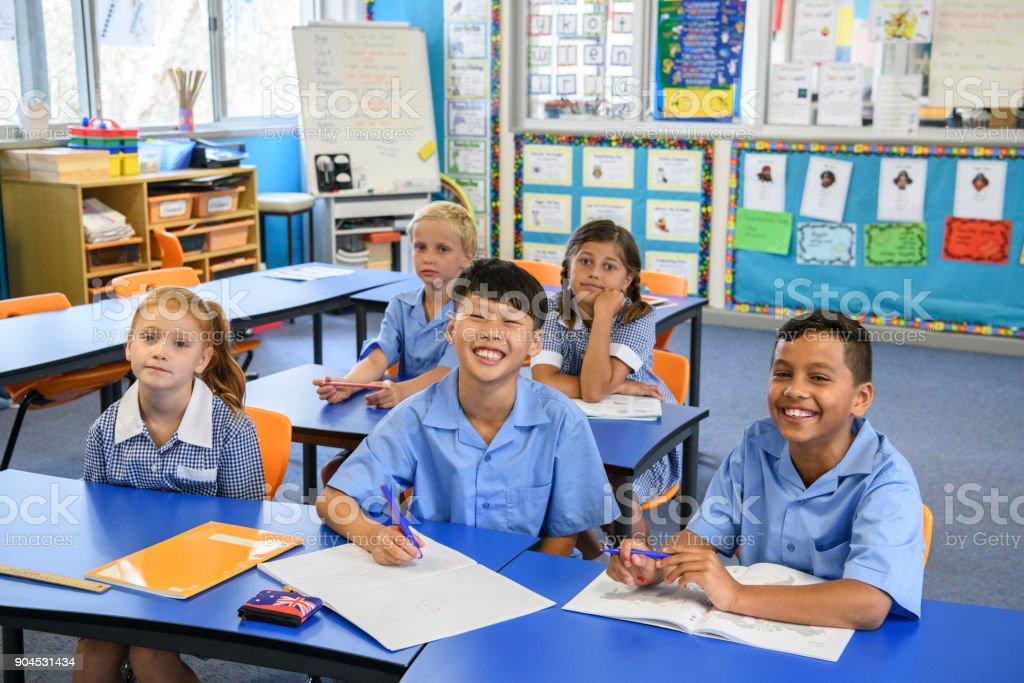Portrait of five multi racial school children sitting at desks in clasroom stock photo