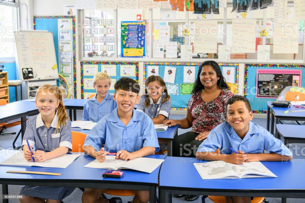 Portrait of five primary school children in classroom with their teacher stock photo