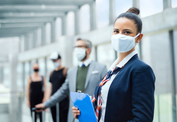 Portrait of flight attendant standing on airport, wearing face masks. stock photo
