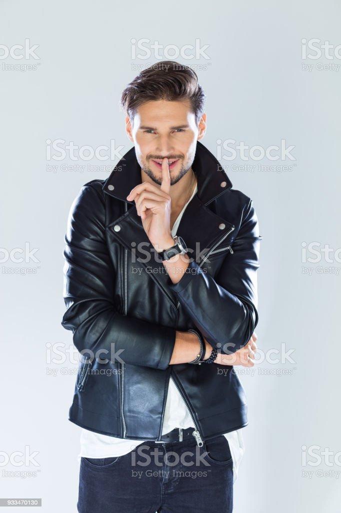 Portrait of flirting handsome man wearing leather jacket Fashion portrait of handsome man wearing black leather jacket. Studio shot, grey background. 25-29 Years Stock Photo
