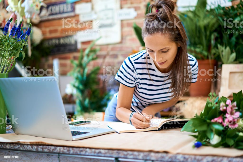 Portrait of florist writin in notebook while leaning against counter with laptop stock photo