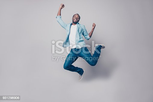 925466128istockphoto Portrait of flying, crazy, carefree, free, cheerful, funny man in sneakers, denim outfit, jumping with raised arms, celebrating victory, having fun, rest, relax, leisure, isolated on grey background 931298906