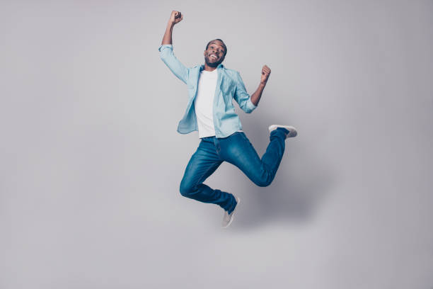 Portrait of flying, crazy, carefree, free, cheerful, funny man in sneakers, denim outfit, jumping with raised arms, celebrating victory, having fun, rest, relax, leisure, isolated on grey background Portrait of flying, crazy, carefree, free, cheerful, funny man in sneakers, denim outfit, jumping with raised arms, celebrating victory, having fun, rest, relax, leisure, isolated on grey background yeah right stock pictures, royalty-free photos & images