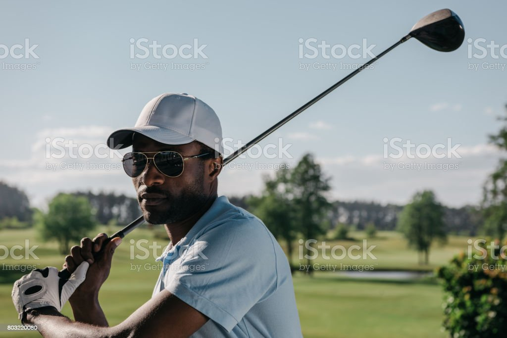 portrait of focused african american man playing golf at golf course stock photo