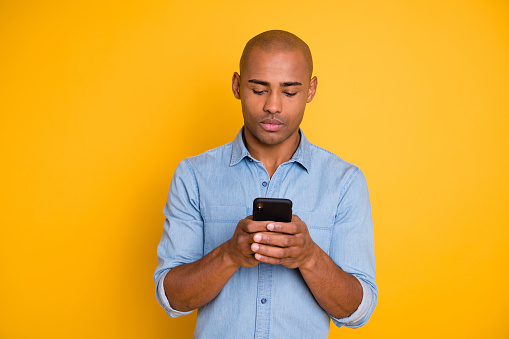 istock Portrait of focused handsome youth hod hand modern technology search information isolated over yellow background 1163694423