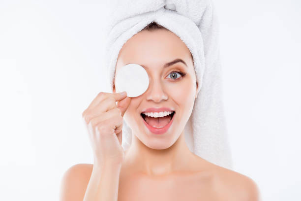 portrait of foolish playful woman using sponge for application of lotion close one eye with cotton keeping open mouth with towel on head isolated on white background. - smile woman open mouth foto e immagini stock