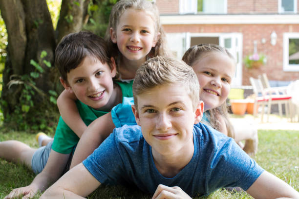 Portrait Of Four Brothers And Sisters Lying In Garden At Home Portrait Of Four Brothers And Sisters Lying In Garden At Home sibling stock pictures, royalty-free photos & images