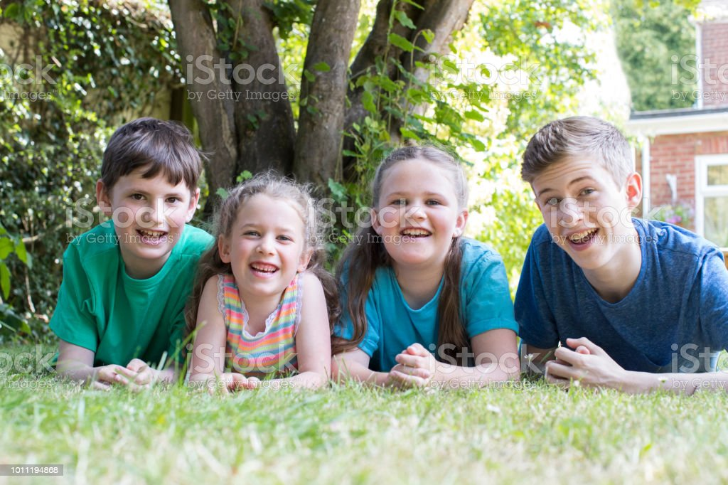 Portrait Of Four Brothers And Sisters Lying In Garden At Home