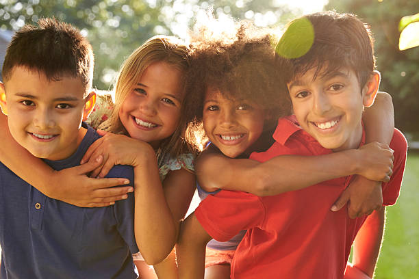 Portrait Of Four Children Having Fun Outdoors Together stock photo