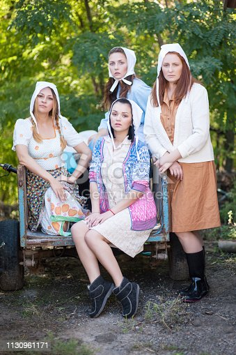 Portrait of four women dressed in a rural retro style. Countryside farm.