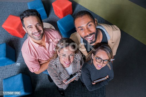 Portrait of four workers in their cowork space. They all appear smiling looking at the camera, dressed in office clothes