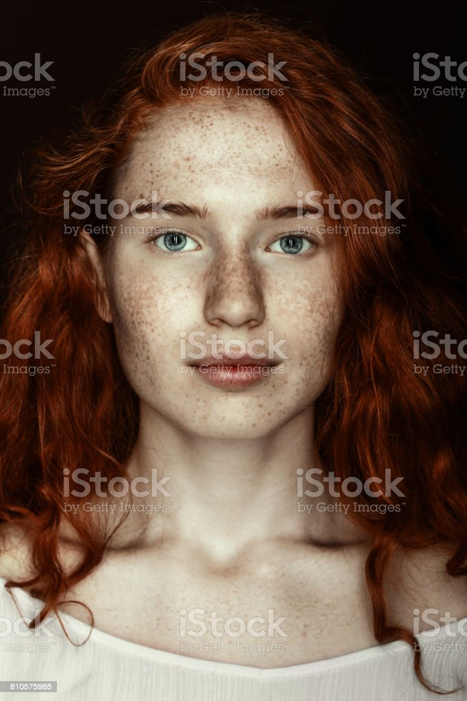 portrait of freckled redhead woman looking at camera, isolated on black stock photo