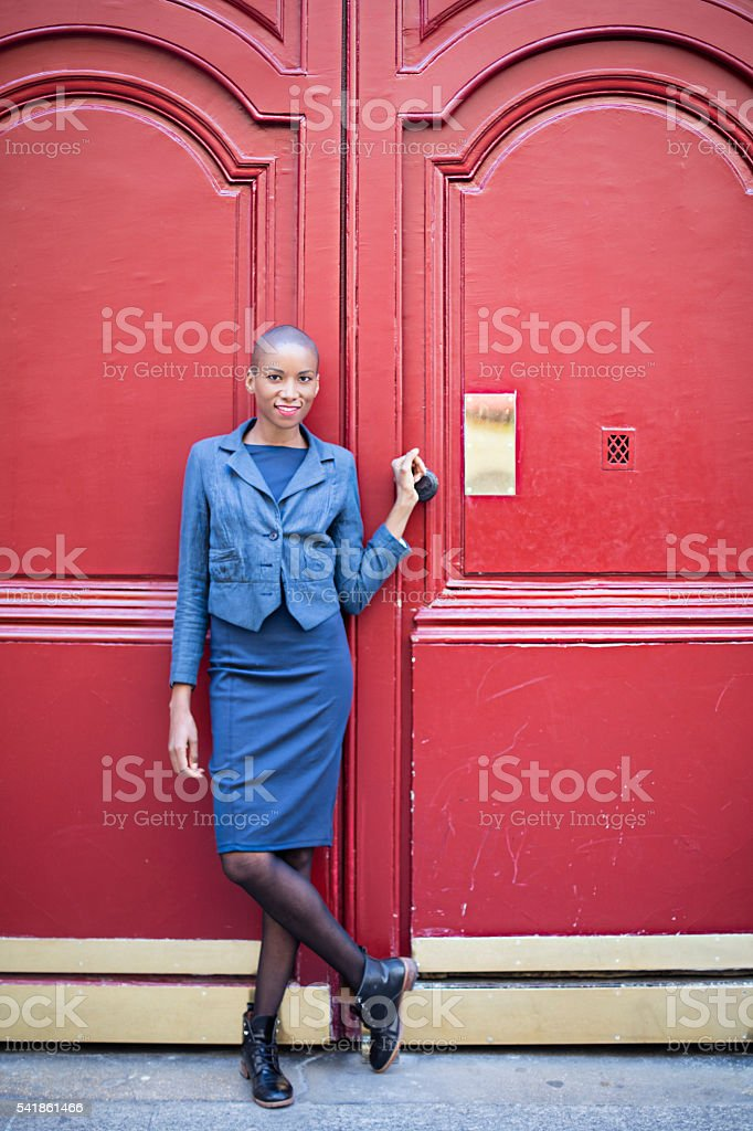 Portrait of french woman in front of wooden red door stock photo