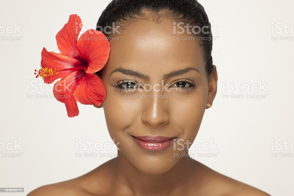 Portrait of fresh clear woman face with hibiscus flower. stock photo