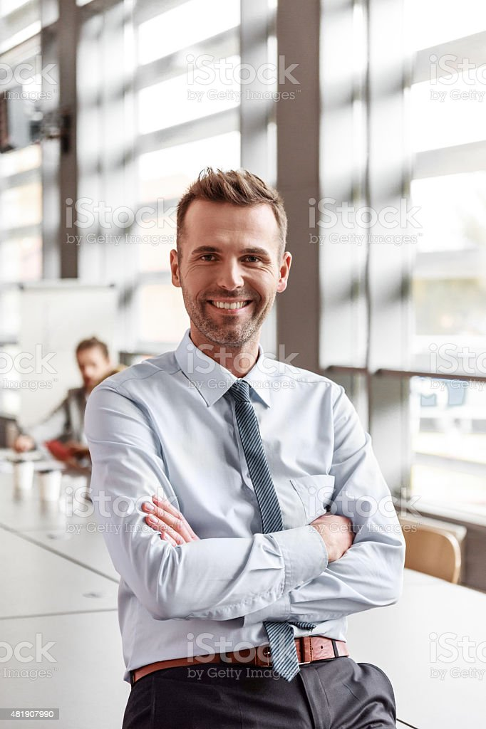 Portrait of friendly businessman in the office Portrait of friendly businessman wearing shirt and tie sitting in the board room with arms crossed, smiling at camera. Coworkers in the background. 2015 Stock Photo