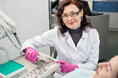 Portrait of friendly female dentist with patient in the dental office. Doctor wearing glasses, mask, white uniform and pink gloves. Dentistry. Dental equipment