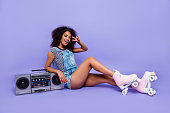 Portrait of friendly girl lean on boom box with cassette tape going to make party on roller skates gesturing v-sign isolated on vivid violent background. Stereo sound song concept
