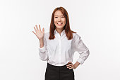Portrait of friendly pleasant and happy young asian woman waving to you as saying hi, greeting newcomers, welcome to team, introduce herself make hello gesture, white background.
