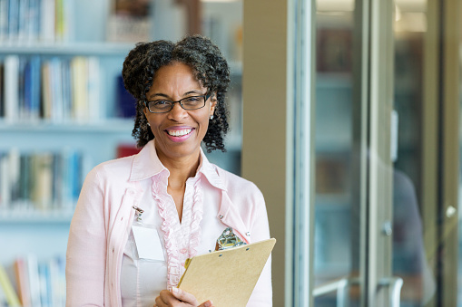 In this portrait, a cheerful librarian stands by her library door and smiles for the camera.  She holds a clipboard.