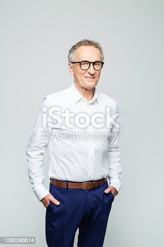 Portrait of elderly elegant man wearing white shirt and glasses smiling at camera. Confident senior businessman, studio shot against grey background.