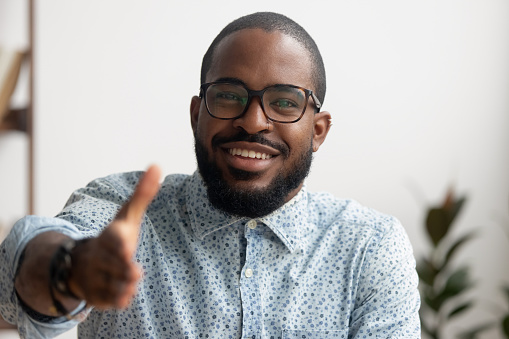 Portrait of smiling African American businessman offering hand for greeting. Friendly black employee ready for handshake, welcoming client, coworker or partner. Successful deal, introduction concept