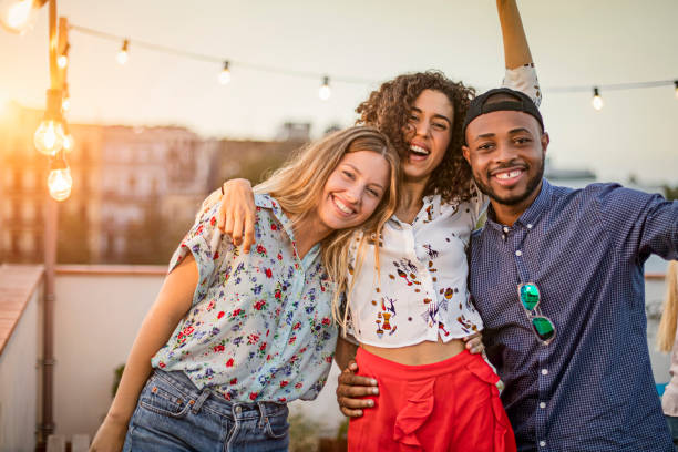 Portrait of friends enjoying in terrace party stock photo
