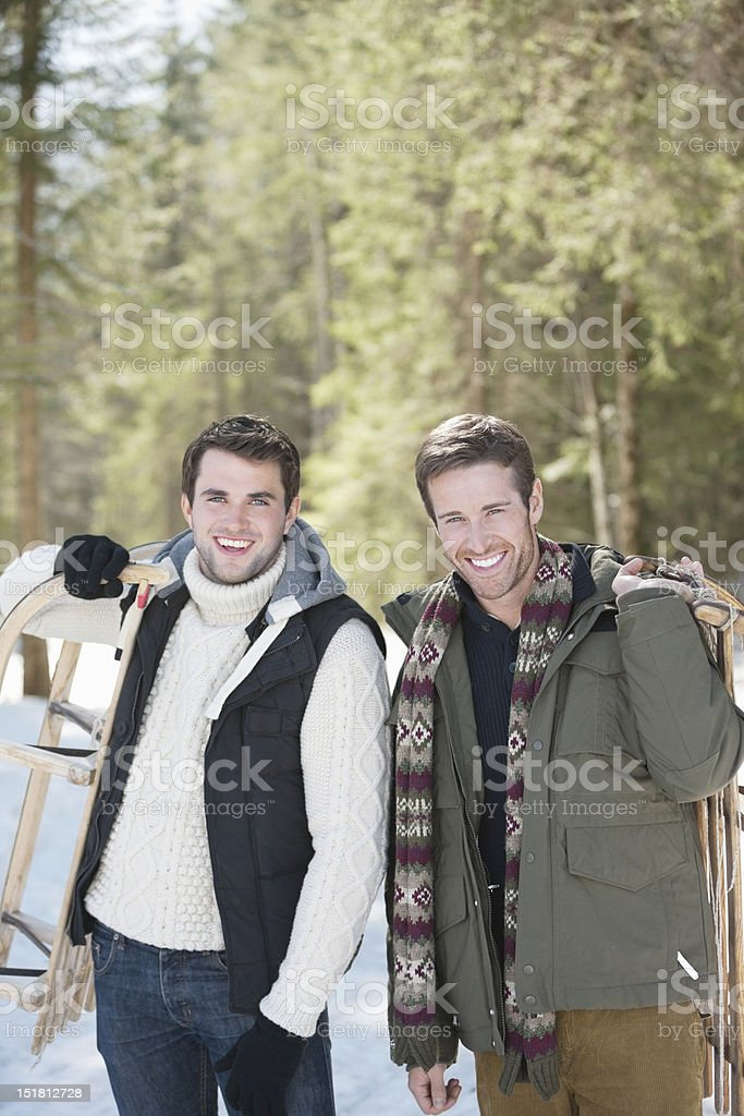 Portrait of friends holding sleds in snowy woods royalty-free stock photo