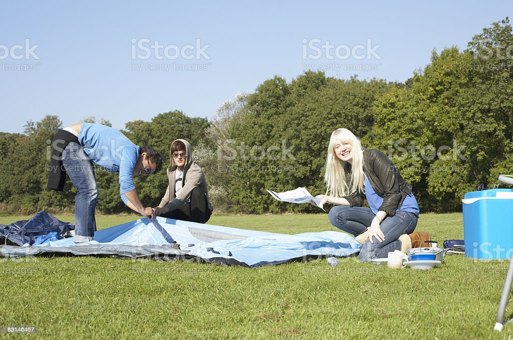 Portrait of friends putting up a tent foto stock royalty-free
