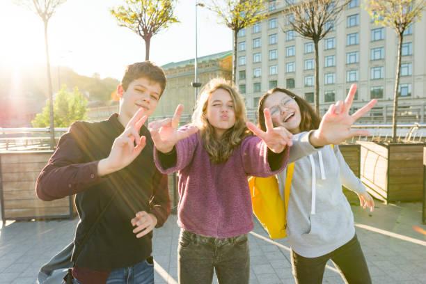 Retrato de amigos adolescentes chico y dos niñas sonriendo, haciendo caras divertidas, mostrando signo de victoria en la calle. - foto de stock