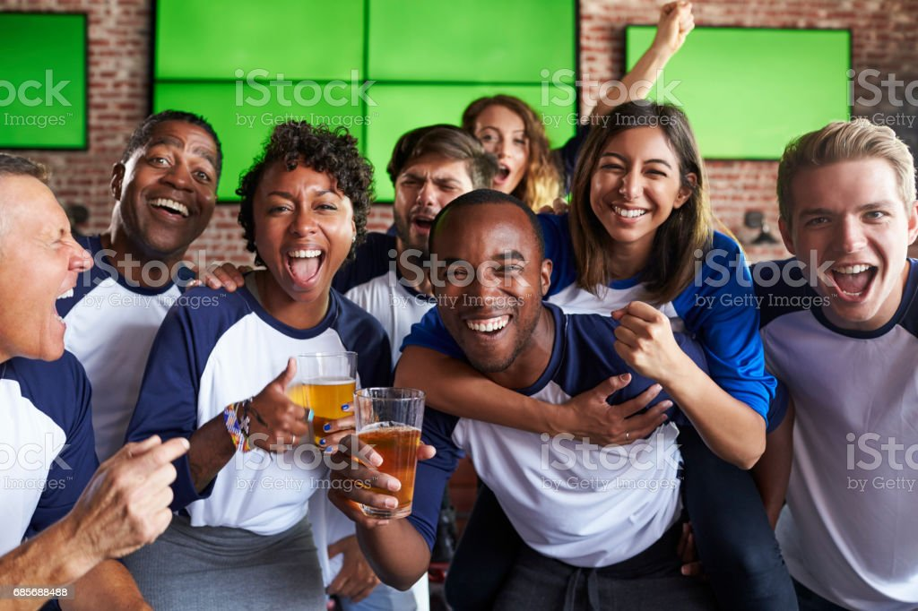 Portrait Of Friends Watching Game In Sports Bar On Screens royalty-free 스톡 사진