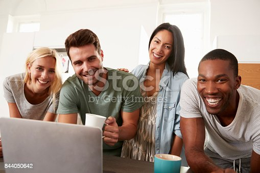 844050630 istock photo Portrait Of Friends With Laptop And Drinking Coffee In Kitchen 844050642