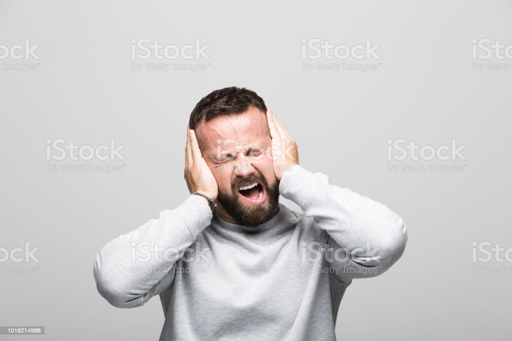 Portrait of frustrated and deserapte bearded young man Exhausted bearded young man shouting at camera with hands covering his ears. Studio shot, grey background. 30-34 Years Stock Photo