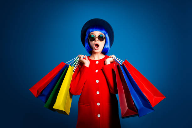 Portrait of frustrated astonishd woman in red coat holding colorful packets in hands having wide open mouth problem  isolated on blue background with shadow and light stock photo