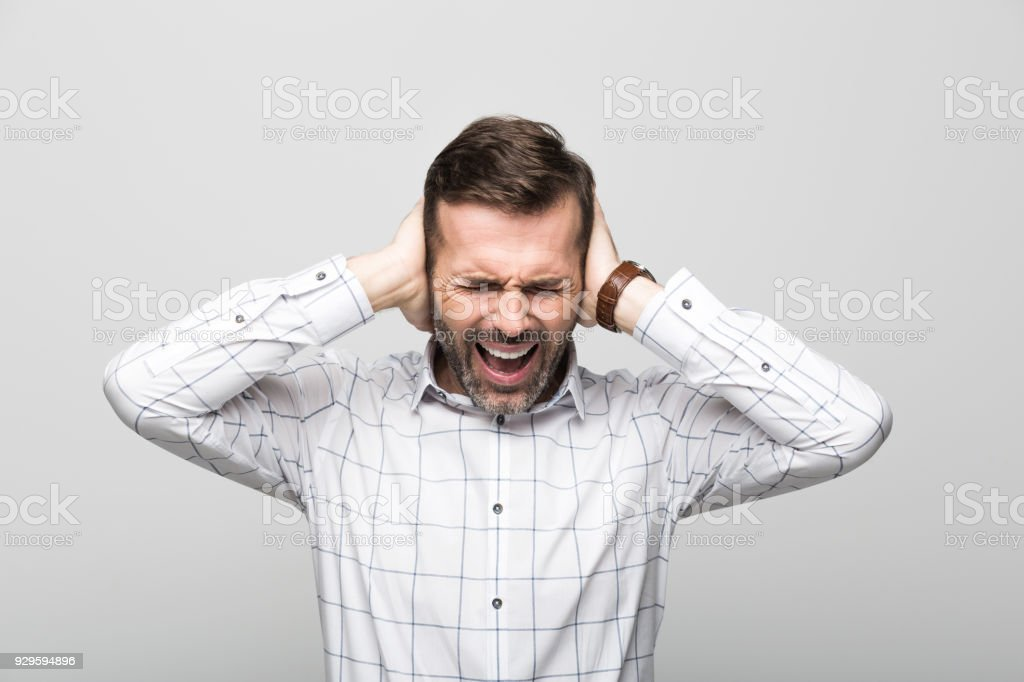 Portrait of frustrated businessman, grey background Studio portrait of frustrated businessman wearing white shirt, standing with hands covering ears against grey background. 30-39 Years Stock Photo
