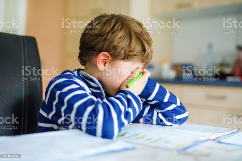 Portrait of frustrated crying sad school kid boy at home making...