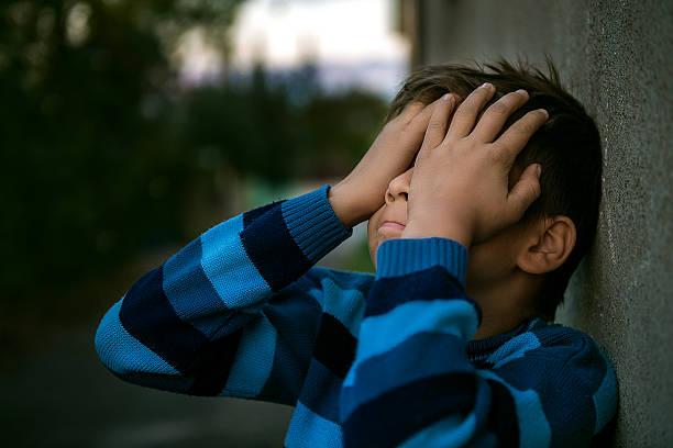 portrait of frustrated little boy covering face in shame - migräne vorbeugen stock-fotos und bilder