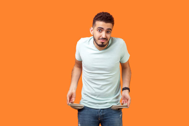 Portrait of frustrated worried brunette man turning out empty pockets. indoor studio shot isolated on orange background Portrait of frustrated worried brunette man with beard in casual white t-shirt turning out empty pockets showing I have no money gesture, bankrupt. indoor studio shot isolated on orange background empty wallet stock pictures, royalty-free photos & images