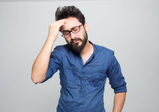 Portrait of frustrated young man over grey background Portrait of frustrated young man over grey  background head in hands stock pictures, royalty-free photos & images