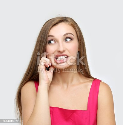istock Portrait of frustrated young woman clenching teeth. 600696272